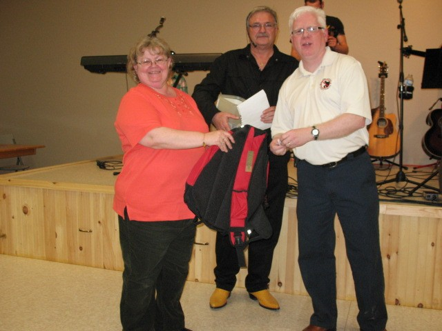 Carol Parker receives one of many door prizes from PEI Crime Stoppers President Gary Bowness with organizer Claude Simpson