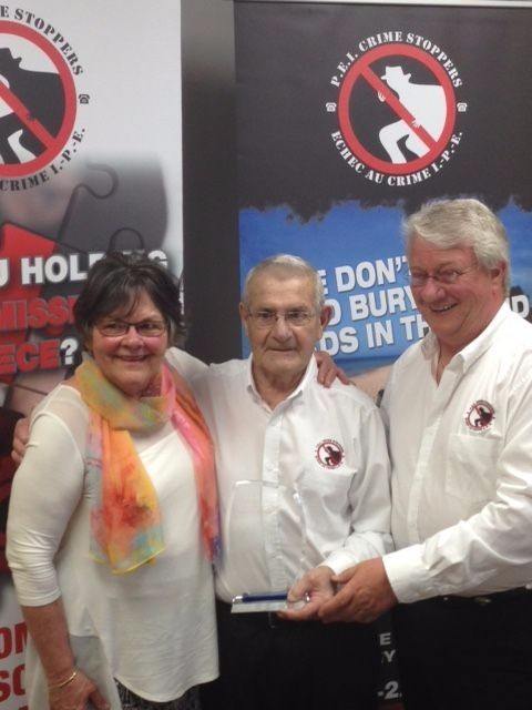Margret MacFarlane and Don Reid, Crime Stoppers President, present the award to Eric Oulton, centre