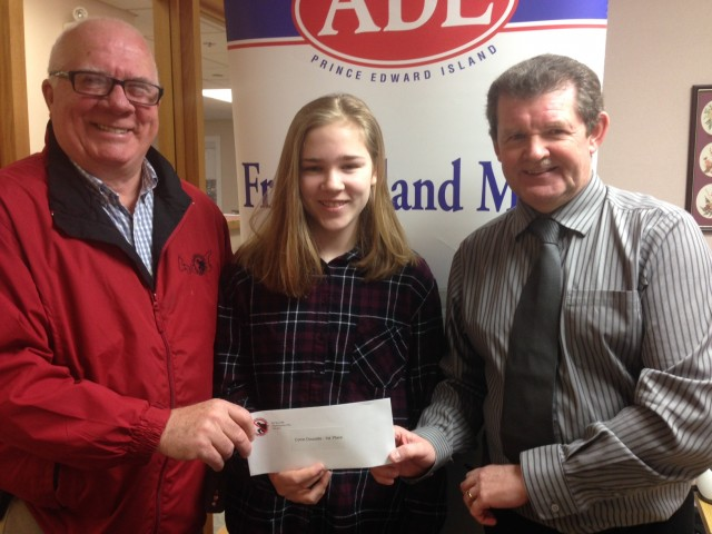 Crime Stoppers Coordinator Phil Pitts (L) and David Doherty(R), Advertising and Marketing Manager at Amalgamated Dairies Ltd.(ADL) present first prize winner, Corrin Doucette, a Grade 11 student at Bluefield High School, with her cheque for the winning design for the 2017 Anti-bullying Pink Shirt.