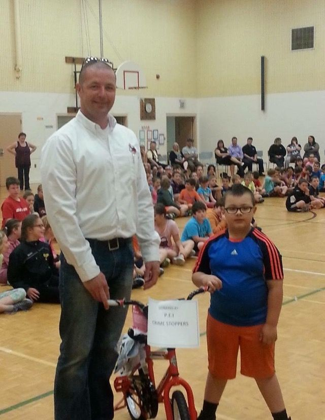 David Casely, PEI Crime Stoppers, presents bike to prize winner Braxton Campbell,
