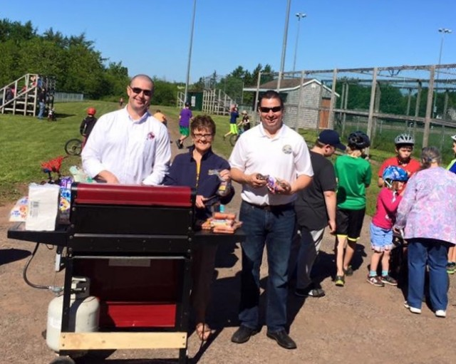 "Kensington Police Bike Rodeo Sponsors Dave Caseley ""PEI Crime Stoppers"" Bonnie MacRae ""Malpeque Bay Credit Union"", Matthew Mackay ""MLA for Kensington/Malpeque"" manning the bbq."