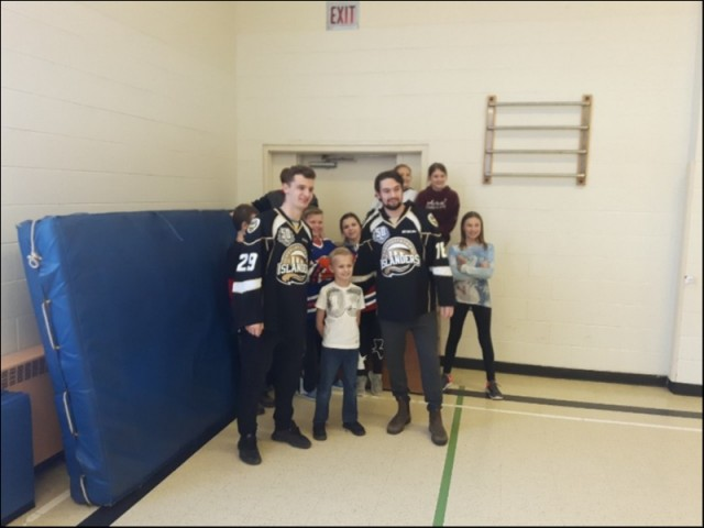 (L-R) Cole Edwards and Jordan Maher of the Charlottetown Islanders Hockey team with the smallest member of the Grade Six class of Cardigan Consolidated, 12 Feb 2019.