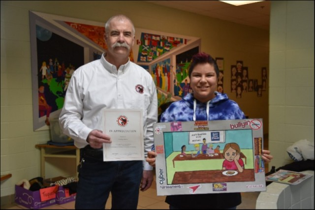 Provincial Coordinator pictured with a grade 7 student at Ecole Sur Mur in Summerside, Brooklyn Blouin. Brooklyn is holding a poster that she designed as part of the Pink Shirt Design Contest. The judges realized that the poster was too detailed to put on a shirt, but felt it accurately expressed one of the many ways Bullying can marginalize some students in their own school.  The poster has been re-produced by Crime Stoppers and will be circulated to as many schools as possible.  Brooklyn was also presented with a Certificate of Appreciation for assisting Crime Stoppers in promoting the elimination of Bullying in Island Schools.
