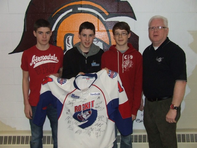 2nd. Place winners from Souris Regional High School received their prize, an autographed PEI Rocket Jersey, from PEI Crime Stoppers President Gary Bowness. (L to R: Max Cahill, Riley Sweeney, Matt MacLean and Gary Bowness)