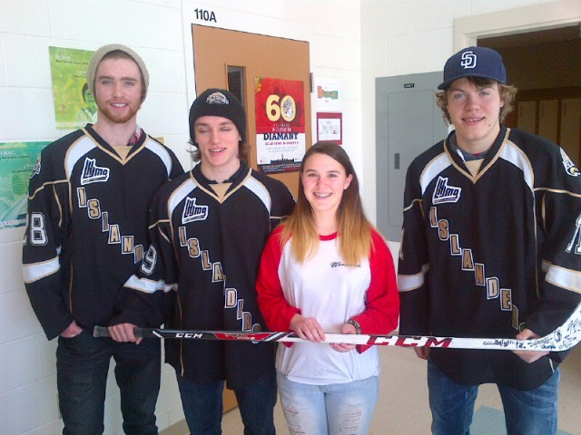Players L to R: Zack Beaton, Nathan Yetman and Daniel Sprong present autographed stick to 2nd. place winner Gabbie Richard.