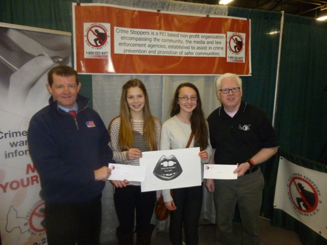 Presentation to first place winners: L to R: Dave Doherty, ADL contest sponsor, Tara Turbide, Sarah MacWilliams and Gary Bowness, President PEI Crime Stoppers.